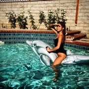 Sarah Hyland - In the pool riding a dolphin